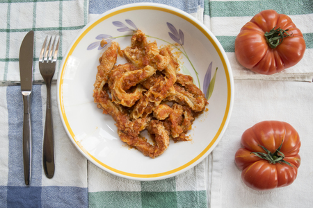dish of tripe roman style with nearby two fresh tomatoes