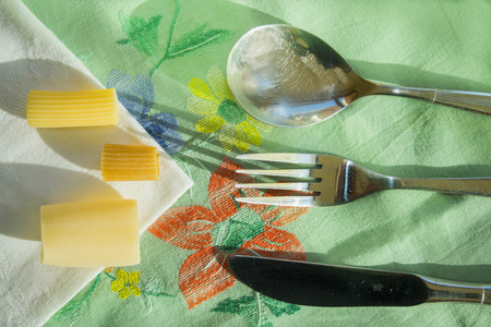 geometric composition with top view between raw pasta and silver cutlery