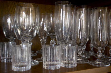 series of wineglasses and crystal wine balloons in a credenza Stock Photo