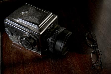 Vecchia macchina fotografica e un paio di specifiche su una credenza in legno Archivio Fotografico - 94686553
