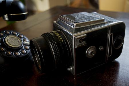 Vecchia macchina fotografica e antico telefono su una credenza in legno Archivio Fotografico - 94593741
