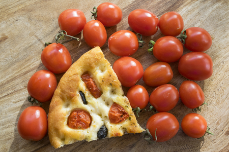 wedge of flatbread or focaccia with cherry tomatoes