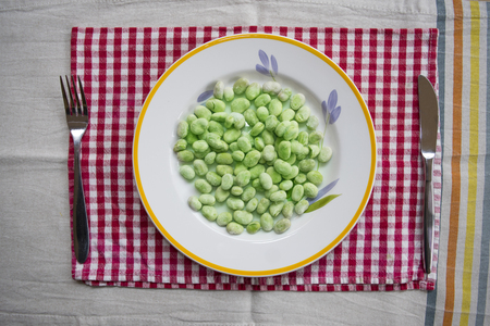 top view on frozen peeled broad beans in a white dish