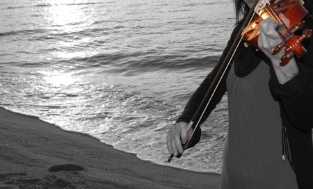 young girl playing the violin by the sea with black and white background