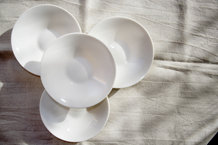 four superimposed white saucer on a grey background