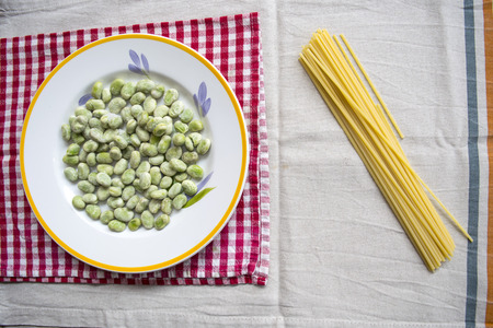 dish of broad beans with near some raw spaghetti pasta