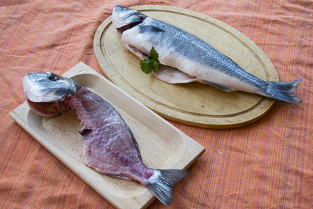 coupled of gilthead already filleted and whole sea bass on wooden bases