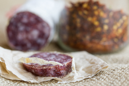 slice of hot salami with crushed hot pepper on a background Banque d'images - 100154801