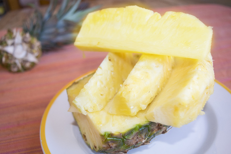 heap of fresh sliced pineapples in a white dish Stock Photo