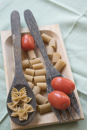 wholemeal butterfly pasta on a wooden ladle and fresh cherry tomatoes