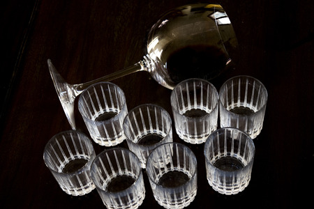 crystal ballon and liquor glasses in semi-darkness on a wooden dish 免版税图像
