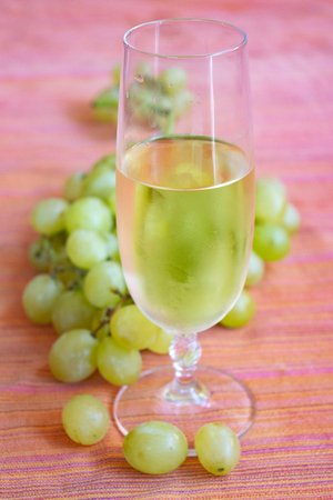 flute of white wine and bunch of grapes for a  concept of grape harvest Standard-Bild - 115910783