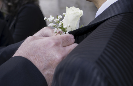 groom wears the boutonniere in a buttonhole