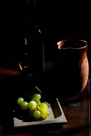 concept of havest with a bunch of grapes in light and shadow