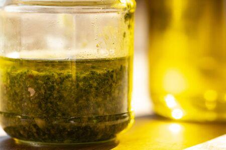 handmade basil pesto in a glass jar near some oil bottles