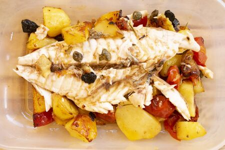 sea bream fillet at the mediterranean style with potatoes and pachino tomatoes