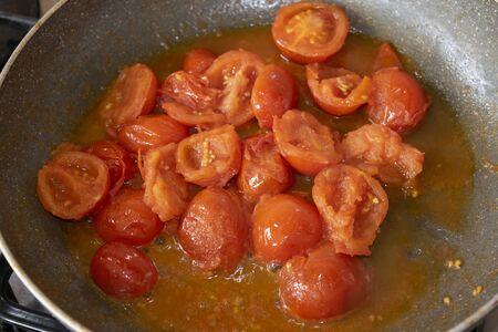 preparing sauteed cherry tomato sauce in pan  Archivio Fotografico