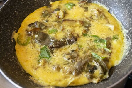 home cooking preparing omelette in pan with onions and basil