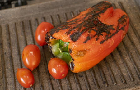 roasting peppers and cherry tomatoes on the griddle