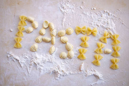 writing pasta between the flour on a wooden board
