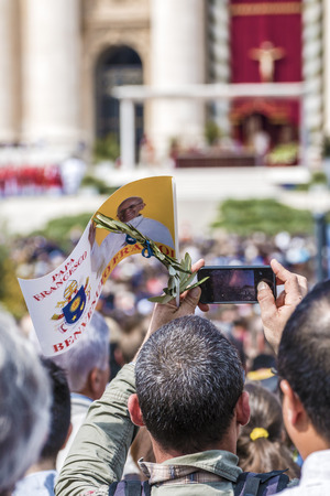 orison: Rome, April 13, 2014: Faithful gathered in St. Peters Square during the Easter celebrations of Palm Sunday celebrated by Pope Francis. A faithful with flag of Pope francis and an olive branch, peace sign, photographing the event. April 13, 2014, Vatican