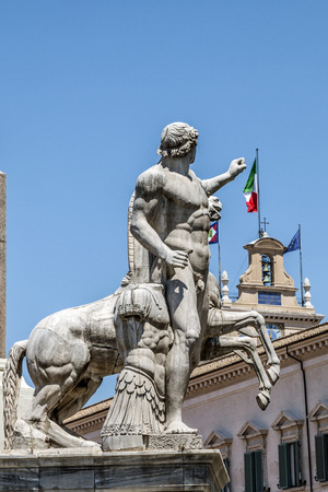 escultura romana: Vista de la plaza del Quirinale con una escultura romana en el fondo y el campanario de la residencia oficial Palazzo del Quirinale del Presidente de la República Italiana