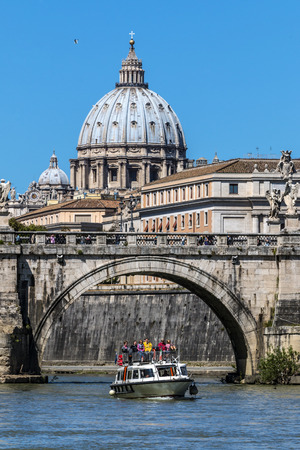 a boat  in the river Tiber near Castel SantAngelo, in the background the imposing presence of the basilica of St. Peters, Rome, Italy Editorial
