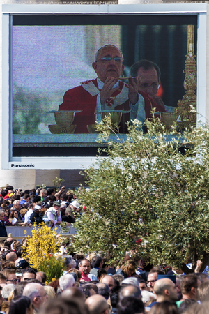 oration: Rome, 13 April 2014: A group of believers, in St. Peters Square on Palm Sunday during the Eucharistic blessing of Pope Francis. Pope Francis on the big screen. April 23, 2014, Vatican City, Italy Editorial