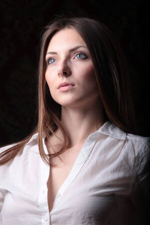 sad girl in a white blouse on a dark background