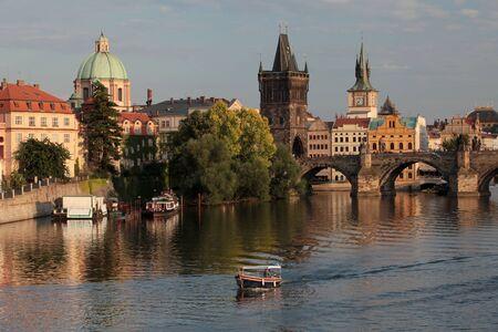 against the current: Prague, Charles bridge, Vltava, boat sailing against the current