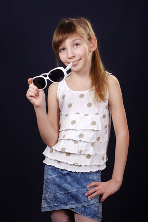 denim skirt: smiling girl in denim skirt holds sunglasses