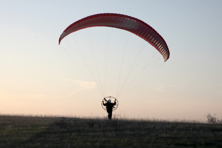 pilot light: the rise of the paraglider with the motor in the rays of the setting sun