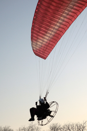 pilot light: the flight of the paraglider with the motor in the rays of the setting sun Stock Photo