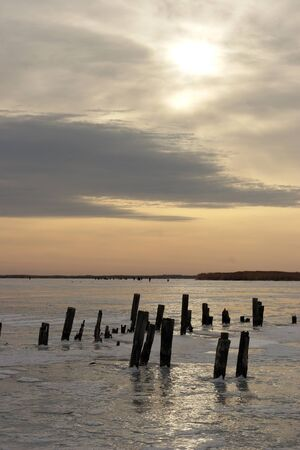 old pier: the remnants of the old pier on the frozen water reservoir Stock Photo