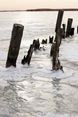 heap of snow: the remnants of the old pier on the frozen water reservoir Stock Photo