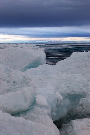hummock: Baikal in April, rainy cloudy weather, the ice is 1 meter, the hummocks on the shore, old ice Stock Photo