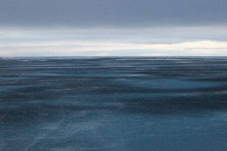 edge of the ice: Baikal in April, rainy cloudy weather, the ice is 1 meter,