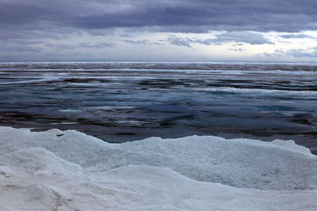 edge of the ice: Baikal in April, rainy cloudy weather