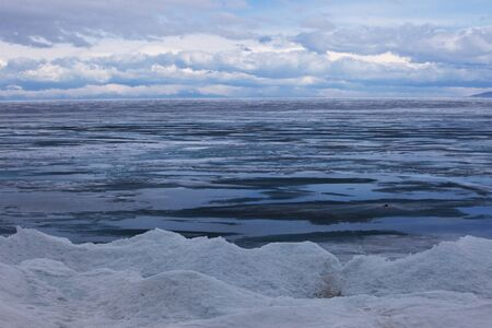 edge of the ice: Baikal in April, a rainy, cloudy weather, ice 1 meter ice on puddles from the rain Stock Photo