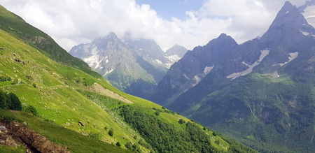 Snow covered mountain peaks in Caucasus. Amazing mountain landscape on sunny summer day.
