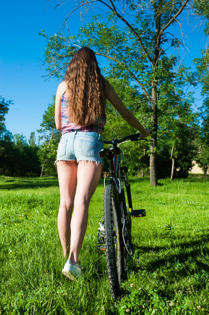 outgoing: Nice girl outgoing with her bicycle at park Stock Photo