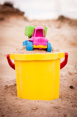 dumptruck: Toy dump-truck in the bucket with sand, summer, day