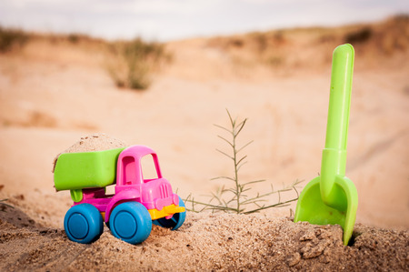 dumptruck: Toy dump-truck in the sands with big spade