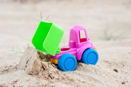 dumptruck: Toy unloading dump-truck in the sands, summer, day