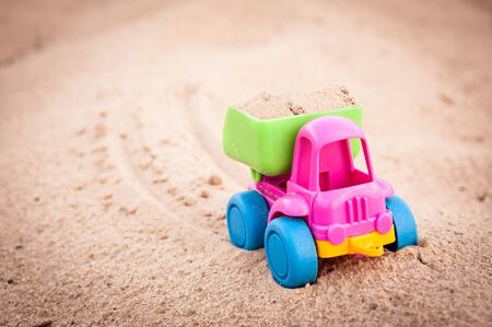 dumptruck: Toy dump-truck in the sands and its trace Stock Photo