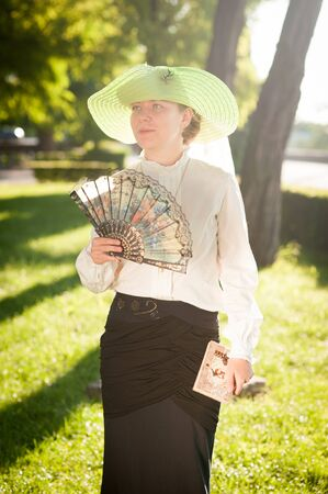 outmoded: Woman with fan in the park, summer day Stock Photo