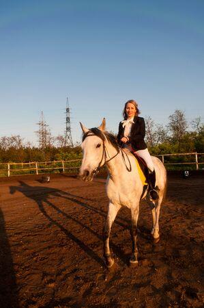 hippodrome: Horsewoman at hippodrome on the blue sky background