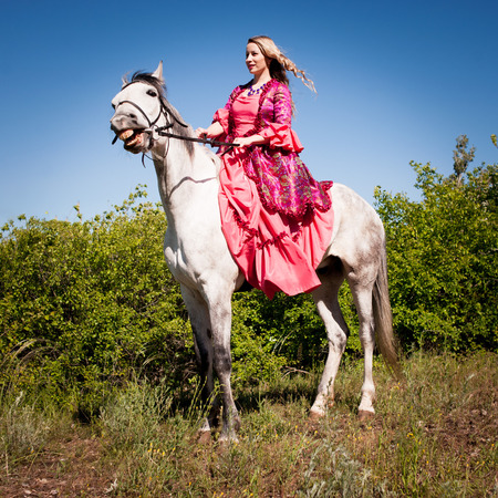 Horsewoman in pink dress on horseback in green forest Stock Photo