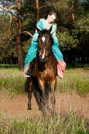 dirtroad: Horsewoman in blue dress riding by the dirt road Stock Photo