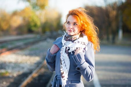 beautiful sunshine: Nice red-haired girl outdoors, autumn trees background. Stock Photo